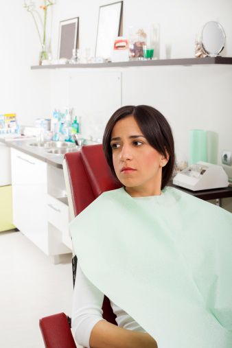 Anxious woman in dental chair benefits from dental sedation by Dr. Djawdan.